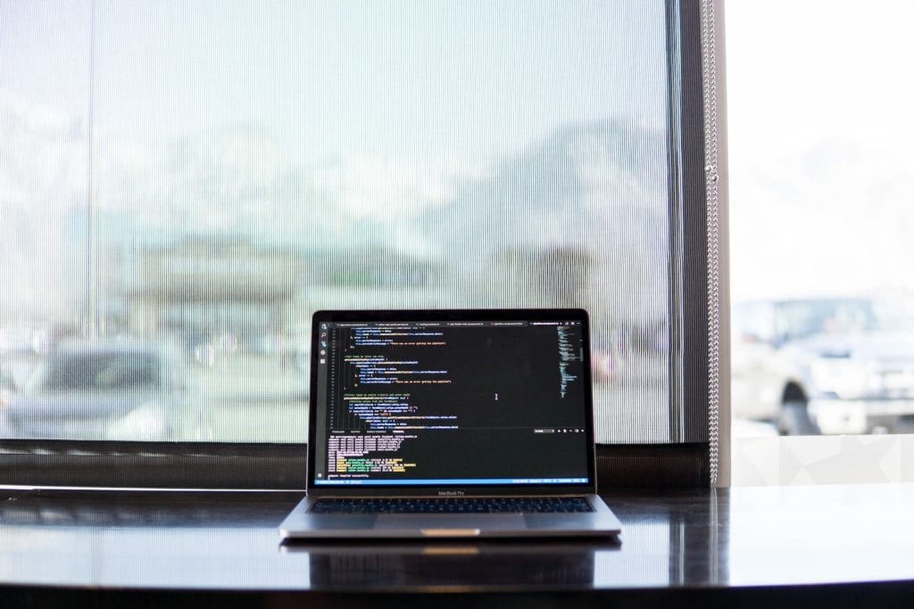 laptop on a desk displaying code on the screen