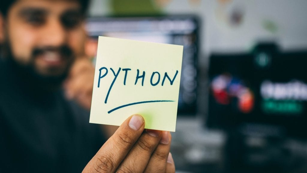 man holding a sticky note with Python written on it