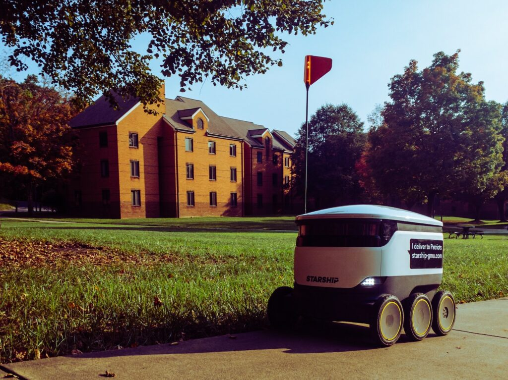Delivery robot parked beside lawn